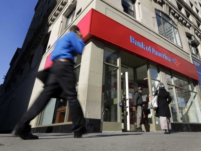 People pass a Bank of America brach, in New York, Monday. Bank of America will pay $10.3 billion to Fannie Mae to settle claims resulting from mortgage-backed investments.