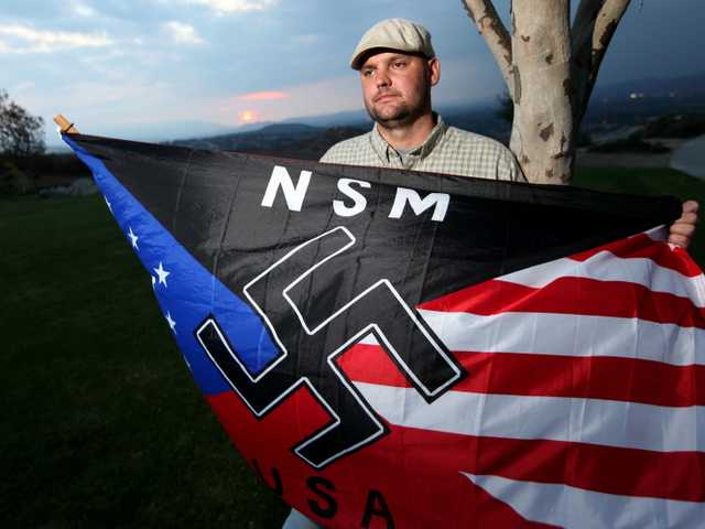 In this Oct. 22, 2010 file photo, Jeff Hall holds a Neo Nazi flag while standing at Sycamore Highlands Park near his home in Riverside, Calif.