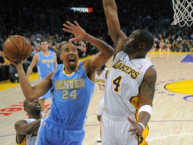 Denver Nuggets guard Andre Miller, center, goes up for a shot as Los Angeles Lakers forward Antawn Jamison on Sunday in Los Angeles.