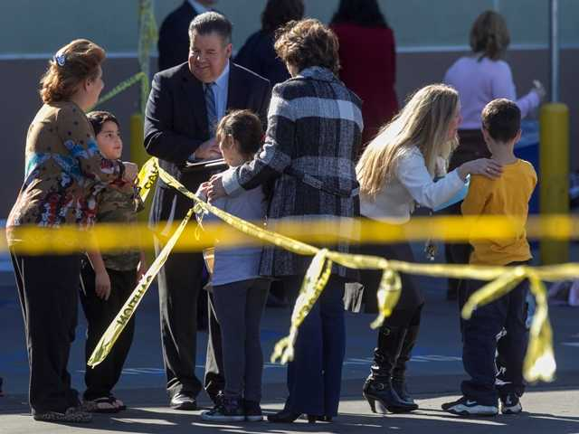 School administrators reunite elementary school children with their parents after their school was evacuated for a bomb threat in Glendale, Calif., Monday.