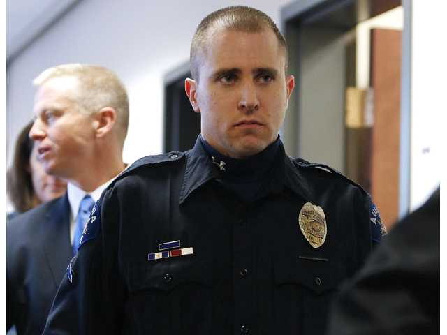 Aurora Police Officer Justin Grizzle leaves court after testifying at a preliminary hearing for James Holmes.