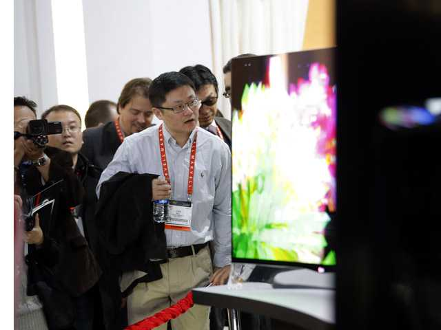 Show attendees look at curved OLED displays at the LG booth at the International Consumer Electronics Show in Las Vegas.