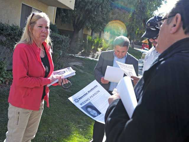 Carol Marino, left, hands out flyers appealing for information about missing 19-year-old Sarah Alarid.