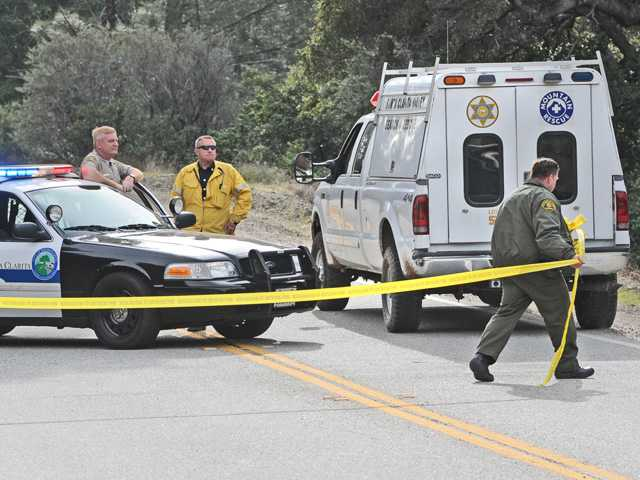 Santa Clarita Sheriff's Deputies move the yellow tape to admit a Santa Clarita Valley Search and Rescue vehicle to the site on Sand Canyon Road in the Angeles National Forest where a car was found down a steep ravine with a body nearby on Wednesday morning.