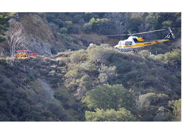 A Los Angeles County Fire Helicopter lowers s a firefighter/paramedic to area where a car and body were discovered down a steep ravine off Sand Canyon road in the Angeles National Forest on Wednesday morning. Photo Rick McClure for The Signal