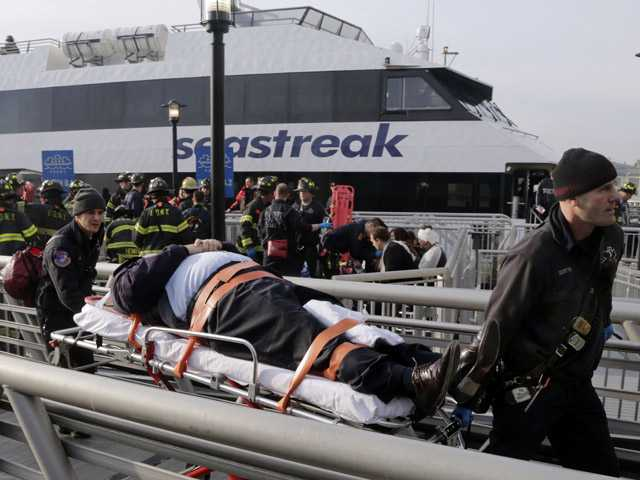 An injured passenger from the Seastreak Wall Street ferry is taken to an ambulance, in New York, Wednesday.