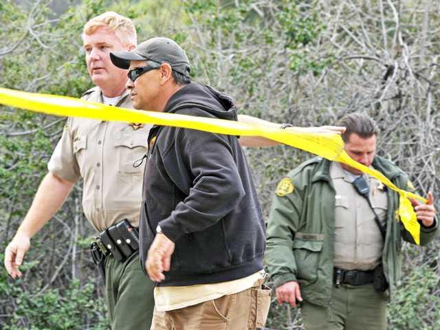 Sheriff's deputies escort Mike Alarid, father of Sarah Alarid, past a roadblock on Sand Canyon Road to be taken toward the crash scene on Wednesday. (Jonathan Pobre/The Signal)
