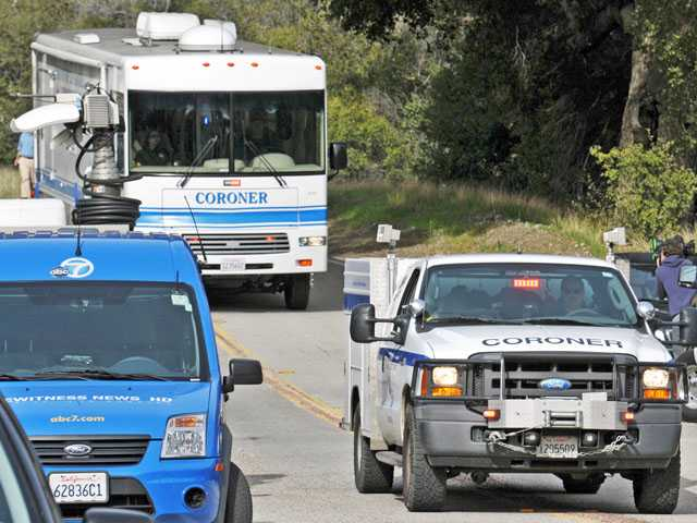 Coroner's officials make their way on Sand Canyon Road toward the scene where Sarah Alarid's body and vehicle were found in a ravine on Wednesday. (Jonathan Pobre/The Signal)