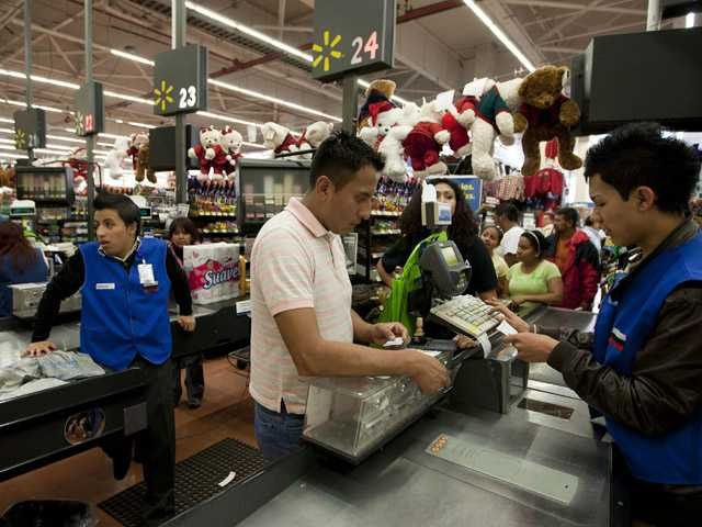 A man pays at the cash register at a Wal-Mart Superstore in Mexico City.