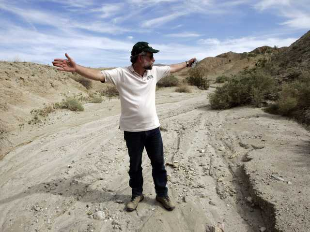 Doug Given, a seismologist and project leader from the U.S. Geological Survey, stands in a dry creek bed and uses his arms to indicate the approximate direction taken by a fault zone of the San Andreas Fault.