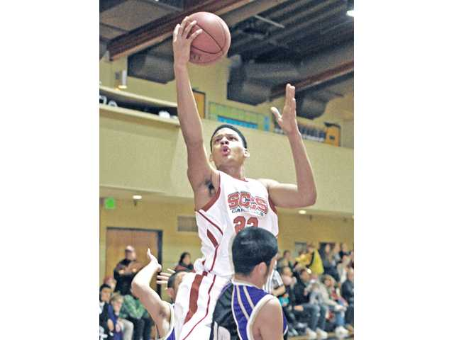 Santa Clarita Christian's Phillip Webb (23) shoots over Vasquez High defenders at SCCS on Thursday.
