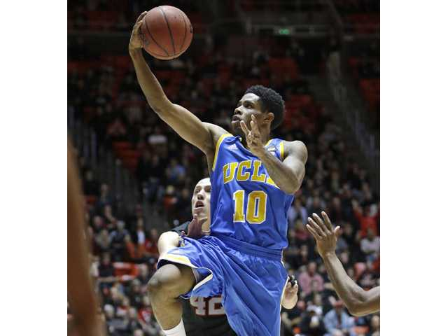 UCLA guard Larry Drew II (10) goes for layup as Utah center Jason Washburn (42) defends on Thursday in Salt Lake City.