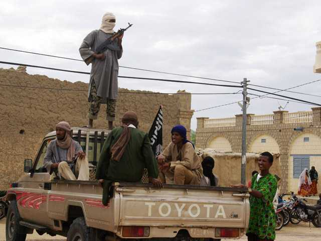 In this 2012 photo, fighters from the al-Qaida-linked Islamist group Ansar Dine stand guard in Timbuktu, Mali.