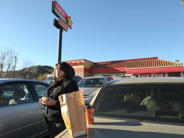 Marlen Angel of Pomona eats breakfast in the parking lot of Carl's Jr. in Castaic, waiting with fellow motorists for the freeway to reopen Friday morning. Signal photo by Jonathan Pobre