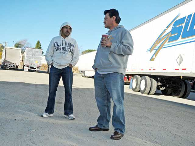 Jose Trinidad, left, and Elias Ambriz talk as they wait for authorities to reopen the northbound lanes of Interstate 5 at Parker Road in Castaic on Friday morning. Signal photo by Jonathan Pobre