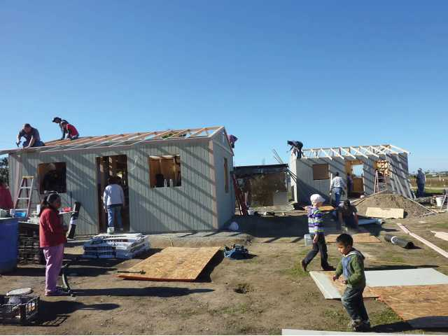 A team of volunteers works to finish roofing two homes in Benito Juarez, Mexico.
