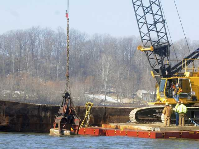 Employees with Durocher Marine pull a rock out of the water in an effort to deepen the waterways on the Mississippi River just outside of Thebes, Ill., on Monday.