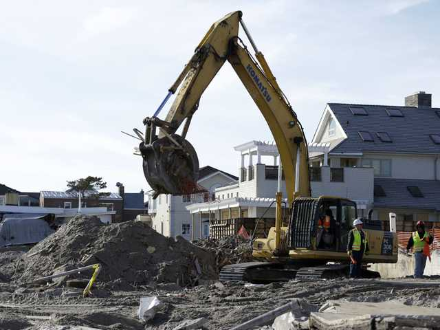 The remains of a house damaged by Superstorm Sandy and then bulldozed by a contractor are removed from the beach in the Belle Harbor section of the Rockaways, as cleanup from the storm continues Thursday, in New York.