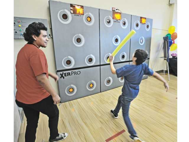 Anthony Saucedo, left, encourages  Roy Garrett, 11, as the competes for points on the XerPro Acitiviy Wall at The Canyon Country Community Center opening Saturday.