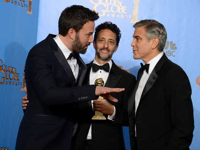 "Actor and director Ben Affleck, left, producers Grant Heslov and George Clooney pose with the award for best motion picture - drama for ""Argo."""