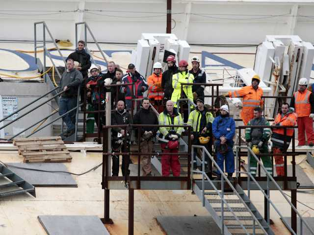 Workers observe a minute silence as they stand on the Costa Concordia cruise ship leaning on its side off the Tuscan Island Isola del Giglio, Italy.