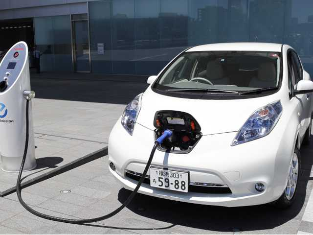 A man demonstrates a quick charge of a Nissan Leaf by a solar-assisted EV charging system at Nissan's global headquarters in Yokohama, Japan, on July 11, 2011.