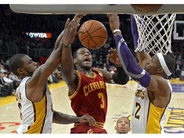 Cleveland Cavaliers guard Dion Waiters, center, goes up for a shot as Los Angeles Lakers forward Earl Clark, left, and center Dwight Howard defend on Sunday in Los Angeles.