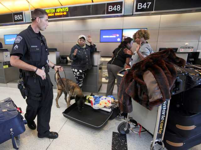 An airport police officer with his search dog Baxo, checks a passengers bag at Los Angeles International Airport.