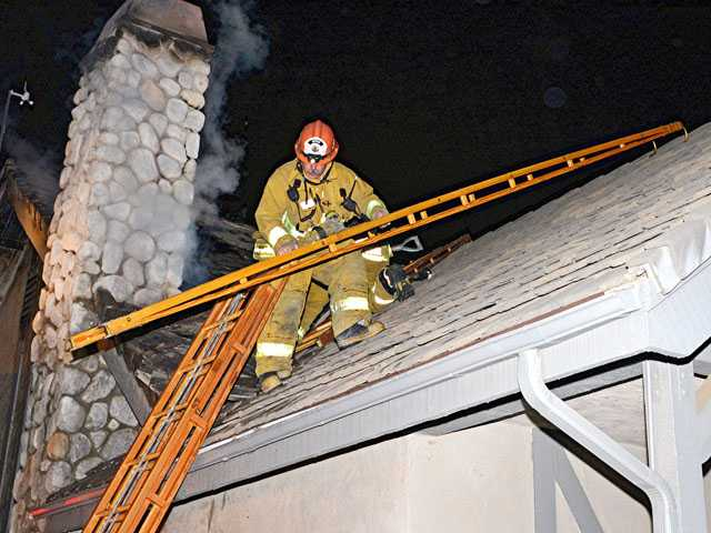 Los Angeles County firefighters battle an attic fire on Sunday night. Photo by Rick McClure/For The Signal