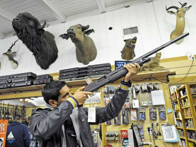 Isaac Cerda, of Canyon Country, examines a Winchester SXP shotgun as he shops in the pro shop at the Oak Tree Gun Club in Newhall on Monday.