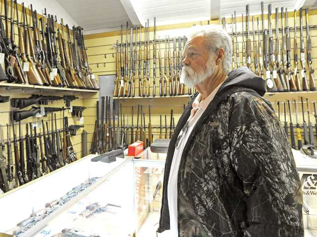 Dave Phillips of Saugus looks through an assortment of firearms for sale in the pro shop at the Oak Tree Gun Club in Newhall on Monday.