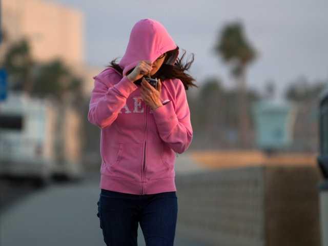 Fiona Chiang shields her face from blowing sand as she walks in Carlsbad, Calif. Thursday. The cold spell that gripped Southern California is easing after hitting a six-year low.