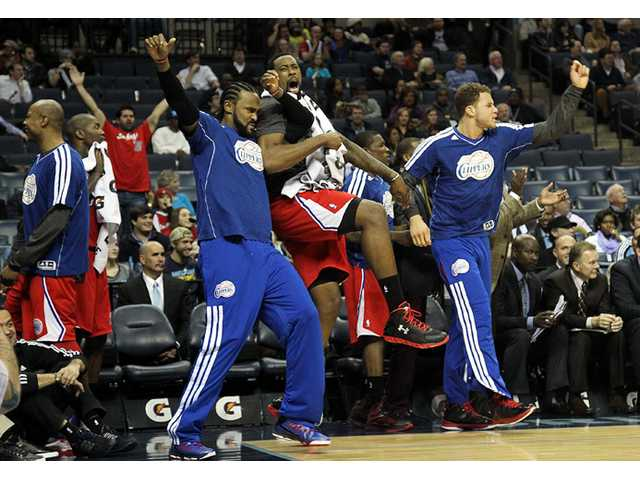 Los Angeles Clippers forward Ronny Turiaf from left, DeAndre Jordan and Blake Griffin react to a teammate's dunk on Monday in Memphis, Tenn.