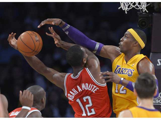 Los Angeles Lakers center Dwight Howard, right, blocks the shot of Milwaukee Bucks forward Luc Richard Mbah a Moute on Tuesday in Los Angeles.