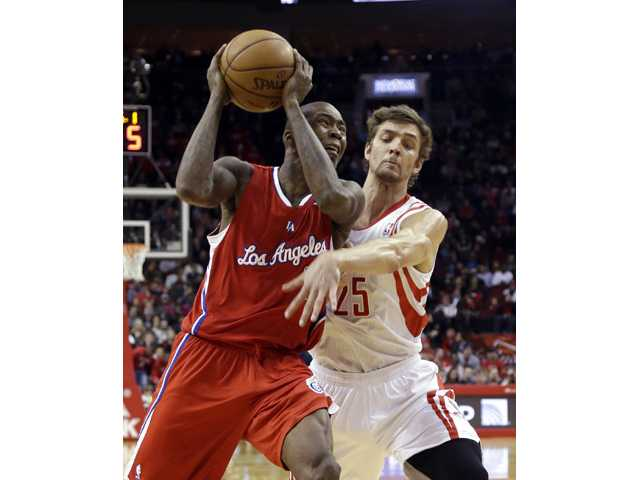 Los Angeles Clipper Jamal Crawford, left, drives toward the basket as Houston Rocket Chandler Parsons (25) defends on Tuesday in Houston.