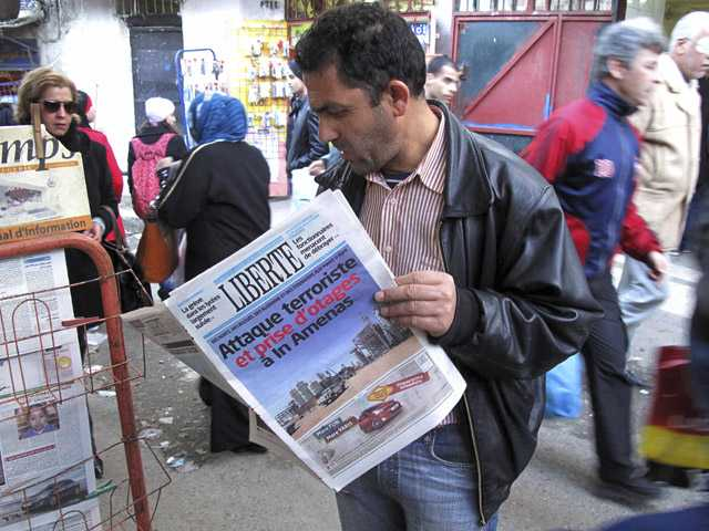 "A man reads a newspaper headlining ""Terrorist attack and kidnapping in In Amenas"", at a news stand in Algiers."