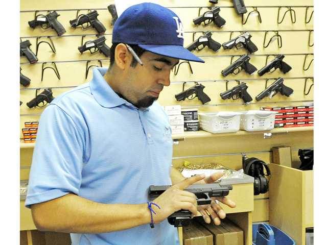Salesman Kirk Marquez examines a Glock 9 mm pistol at the Oak Tree Gun Club in Newhall on Monday.