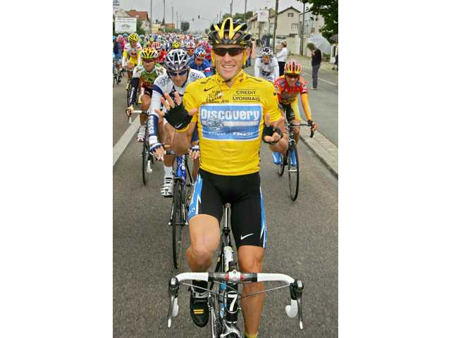 In this 2005 photo, overall leader Lance Armstrong signals seven for his seventh straight win in the Tour de France.