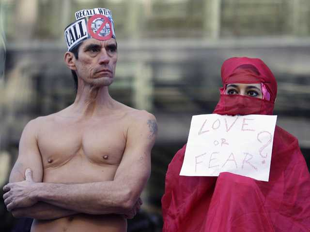 Natalie Mandeau, right, of France, holds up a sign during a demonstration against a nudity ban outside a federal building Thursday.
