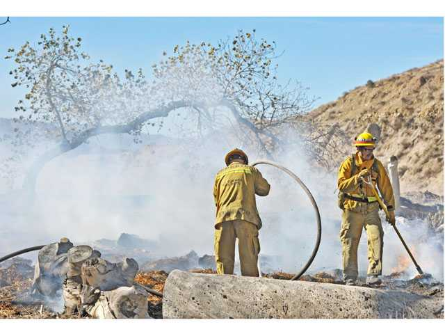 Firefighters mop up after a fire charred brush in a wash near Soledad Canyon Road and Stonecrest Drive in Canyon Country on Thursday morning. (Jonathan Pobre/The Signal)