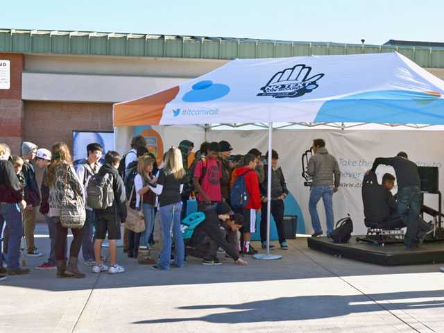 Students wait to try AT&T's No Texting While Driving simulator at Valencia High School on Thursday.