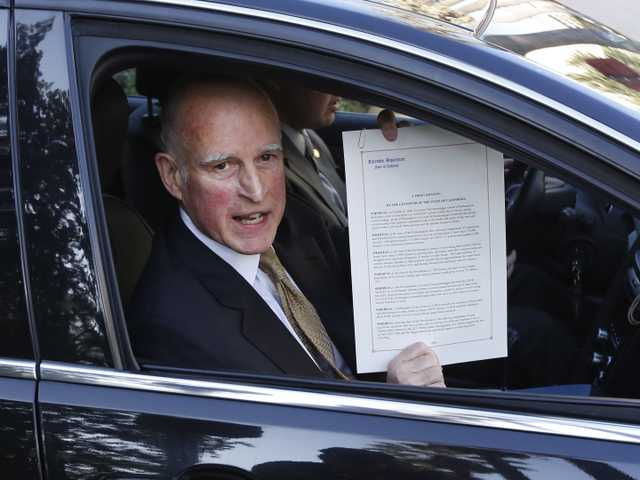Gov. Jerry Brown displays the proclamation he signed declaring the end to the prison overcrowding emergency, as he leaves the Capitol in Sacramento, on Jan. 8, 2013. (AP)