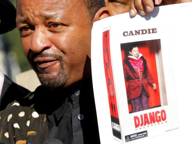 "Community activist Najee Ali holds an action figure depicting Calvin Candie, Leonardo DiCaprio's character from the  film ""Django Unchained."