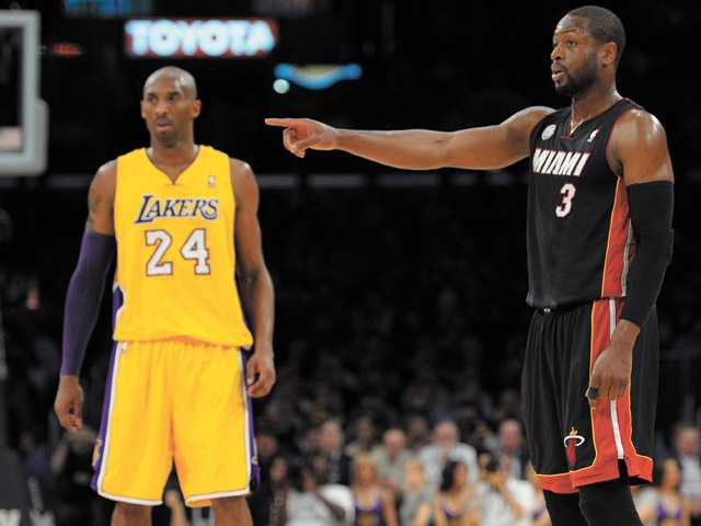 Miami Heat guard Dwyane Wade (3) points as Los Angeles Lakers guard Kobe Bryant (24) stands by Thursday in Los Angeles.