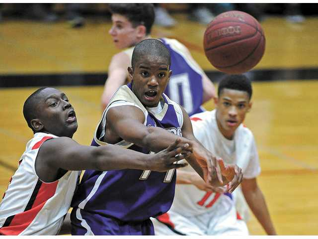 Hart's Stanley Wilder, left, guards Valencia's Kayode Wellington, center, during their game Friday night at Hart High School.