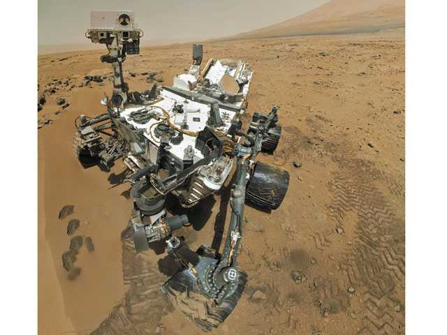 An artist's rendering of the Mars Science Laboratory Curiosity rover examines a rock on Mars with a set of tools at the end of its arm.