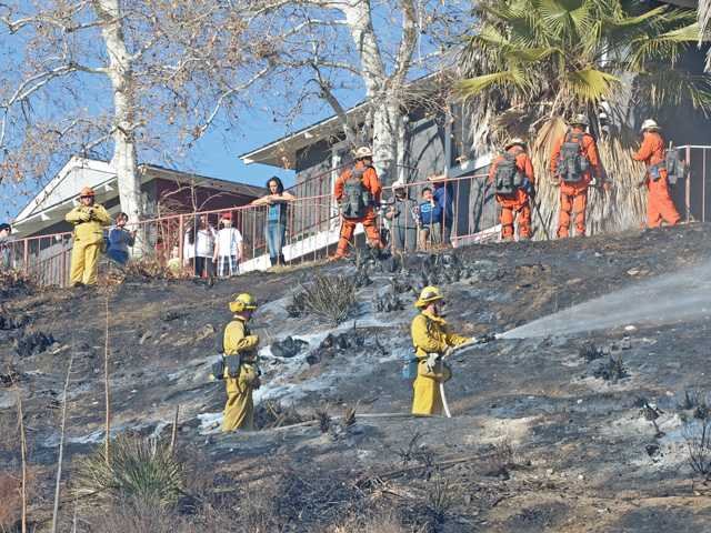 Residents look on as firefighters mop up a quarter acre fire that climbed an embankment  towards apartment buildings above Nadal Street and across from Canyon High School  in Canyon Country on Saturday.