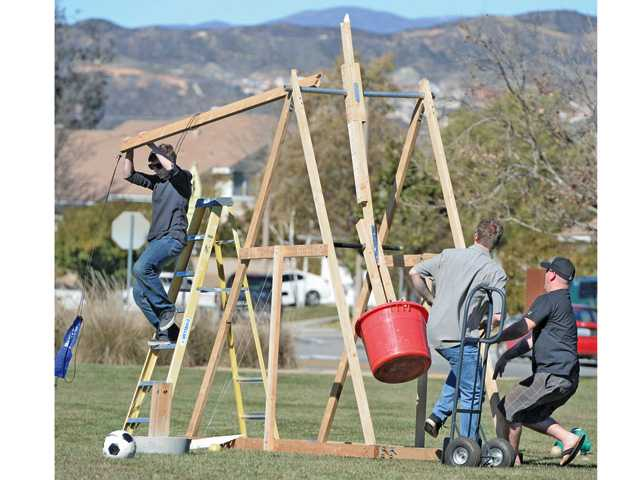 Trebuchet builder Andrew Samson, 17, left, jumps off the ladder as the arm of the trebuchet snaps under the stress of the additional weight as co-builder Christian Brannon, 18, and friend Jeremy Spence, right, add a two-hundred pound weight to the contraption named Iron Breaker during test launches with water balloons and tennis balls at Northbridge Park in Valencia on Saturday.