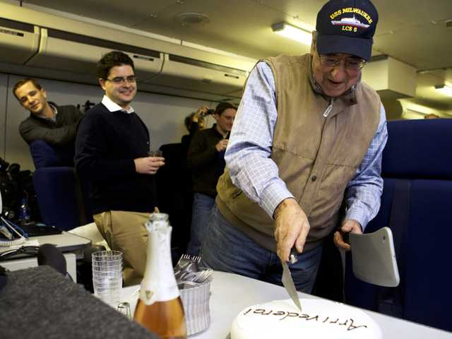"The traveling staff on board the E-4B surprise U.S. Defense Secretary Leon Panetta with a cake that says ""arrivederci,"" in a celebration in honor of the last leg of his final overseas trip as secretary, en route to Washington, Saturday. (AP)"