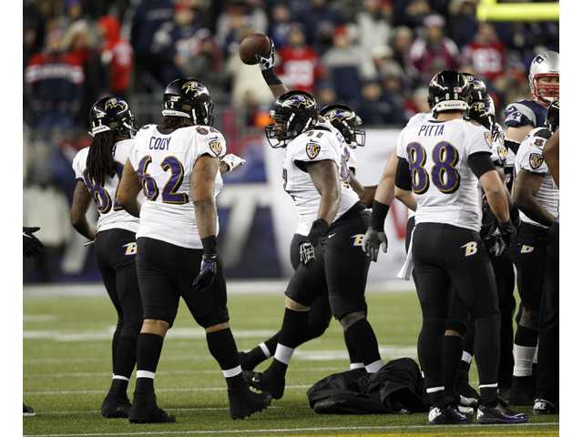 Baltimore Ravens defensive end Arthur Jones, center, celebrates his fumble recovery against the New England Patriots during the AFC Championship in Foxborough, Mass., Sunday.